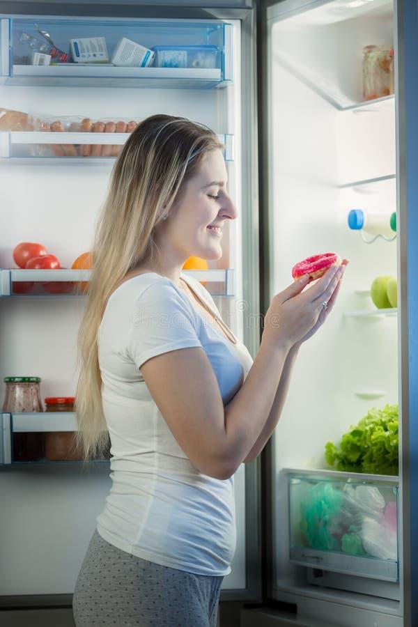Усмехаясь молодая женщина в пижамах стоя на холодильнике на ноче и держать сладостный донут стоковые изображения