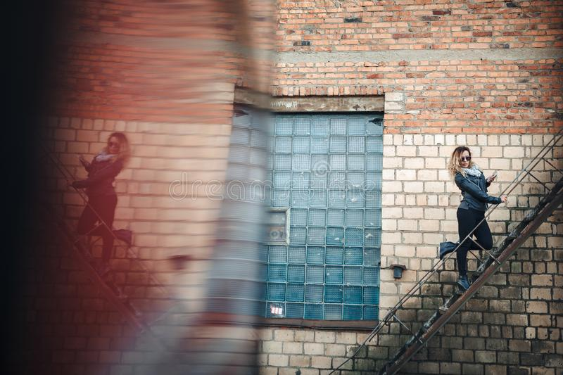 Усмехаясь молодая женщина в солнечных очках, черная кожаная куртка, чернит джинсы стоя на городской лестнице металла против кирпи стоковое изображение rf