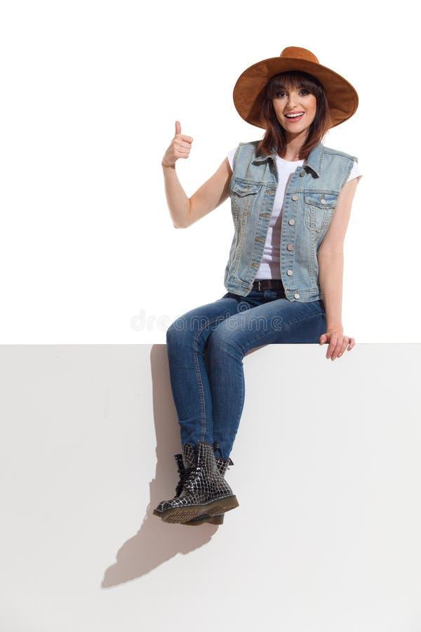 Усмехаясь молодая женщина в шляпе замши Брайна сидит на верхней части знамени и показывает большой палец руки вверх стоковая фотография rf