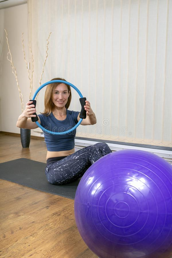 Усмехаясь молодая женщина делая тренировки Pilates стоковая фотография