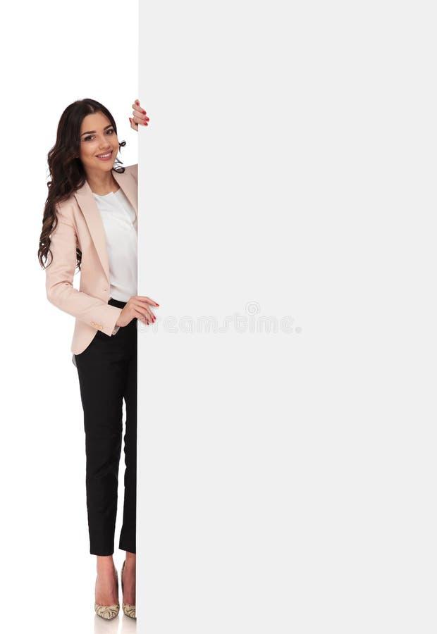 Усмехаясь молодая женщина держа и показывая большой пустой знак стоковое изображение rf