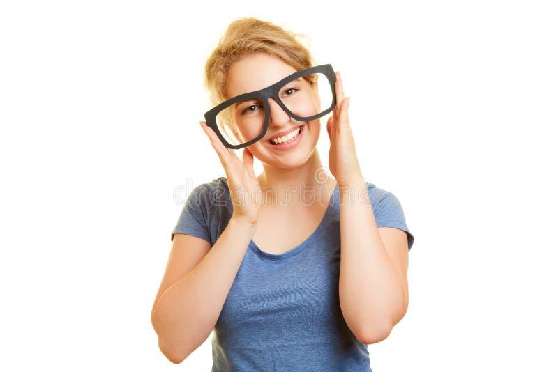 Усмехаясь молодая женщина держит большие стекла как манекен стоковые изображения
