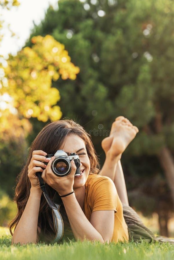 Усмехаясь молодая женщина используя камеру для того чтобы принять фото в парке стоковое фото