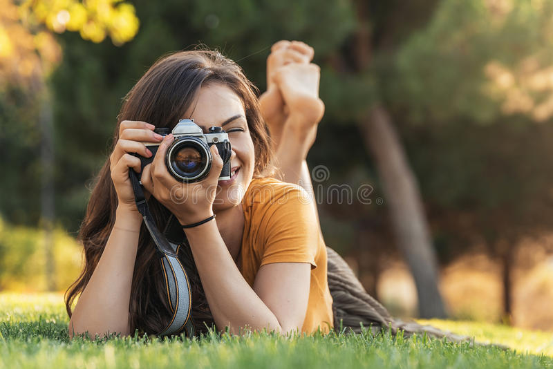 Усмехаясь молодая женщина используя камеру для того чтобы принять фото в парке стоковые изображения