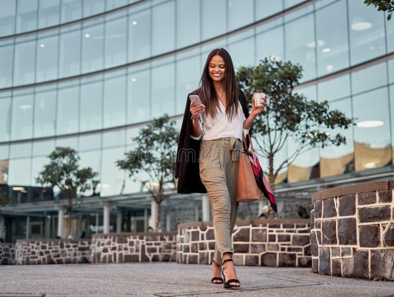 Усмехаясь молодая женщина используя мобильный телефон outdoors в городе стоковая фотография