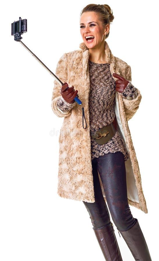 Усмехаясь молодая женщина на белом принимая selfie используя selfie вставляет стоковые изображения rf