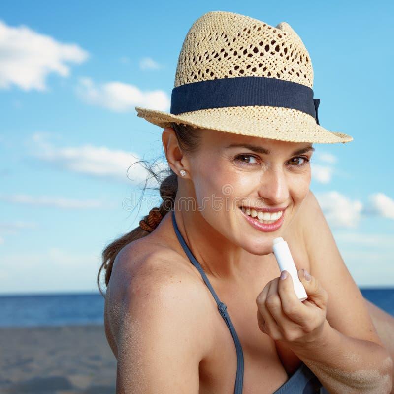 Усмехаясь молодая женщина на пляже прикладывая губную помаду предохранения от солнца стоковое изображение rf
