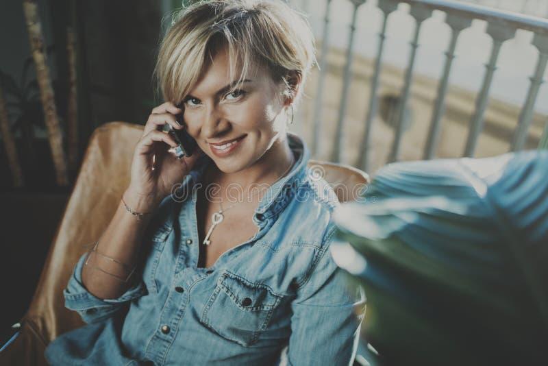 Усмехаясь молодая женщина нося вскользь одежды и говоря на приборе smartphone пока тратящ ослабьте время в перемещении каникул стоковые фото