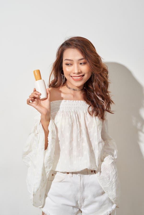 Усмехаясь молодая женщина показывая продукты skincare стоковое изображение rf