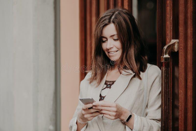 Усмехаясь молодая женщина при темные волосы, одетые в белой элегантной куртке, телефон владениями современный умный, стоит близко стоковая фотография