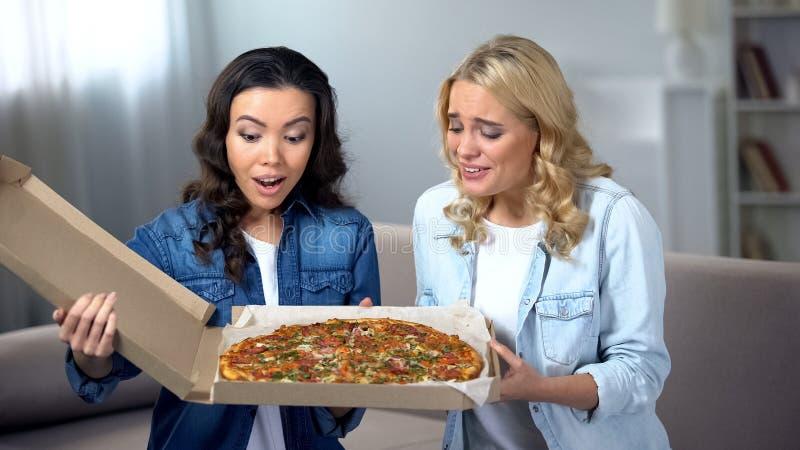 Усмехаясь молодая женщина 2 смотря огромную коробку пиццы, домашнюю партию, доставку еды стоковая фотография rf