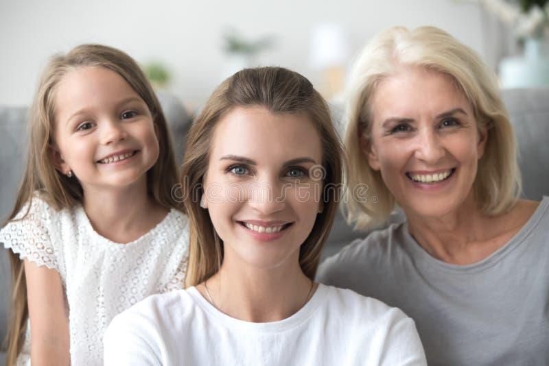 Усмехаясь молодая женщина со старым портретом дочери матери и ребенк стоковая фотография rf