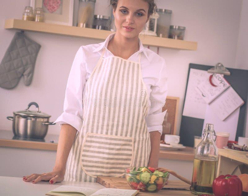 Усмехаясь молодая женщина стоя в кухне стоковые фото