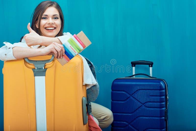 Усмехаясь молодая женщина с 2 выставками чемодана thumb вверх стоковые фото