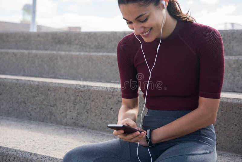 Усмехаясь молодая женщина с телефонами телефона и уха стоковая фотография rf