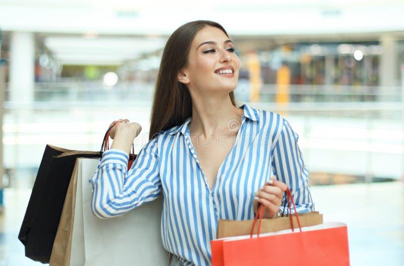 Усмехаясь молодая женщина с хозяйственными сумками над предпосылкой мола стоковое фото