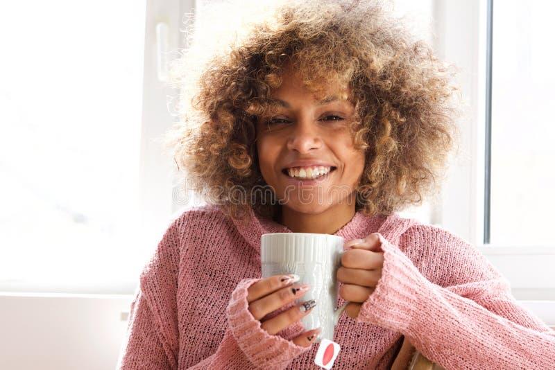 Усмехаясь молодая женщина с чашкой чаю стоковая фотография rf