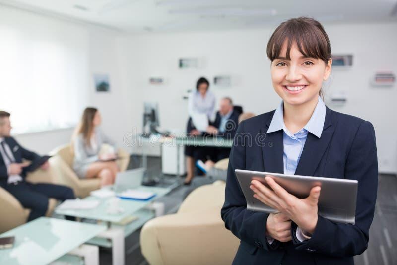Усмехаясь молодая коммерсантка держа таблетку цифров в офисе стоковая фотография rf