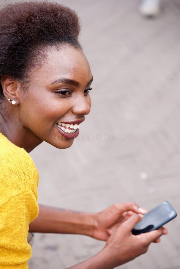 Усмехаясь молодая чернокожая женщина с мобильным телефоном снаружи стоковые фотографии rf