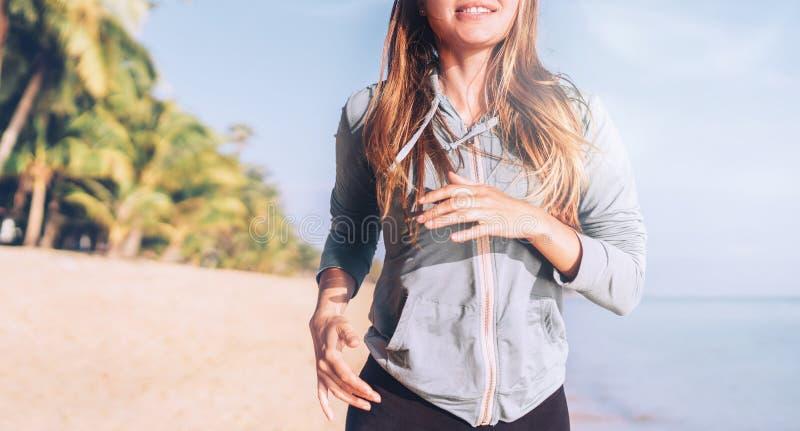 Усмехаясь молодая longhaired женщина имеет утро jogging на пляже взморья стоковая фотография rf