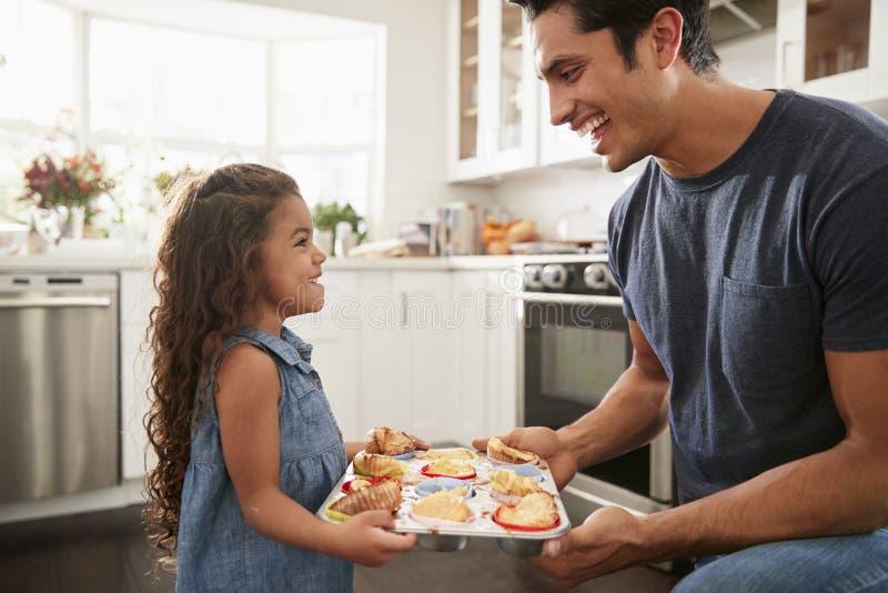 Усмехаясь молодое испанское положение девушки в кухне представляя тортам она пекла к ее отцу стоковое фото