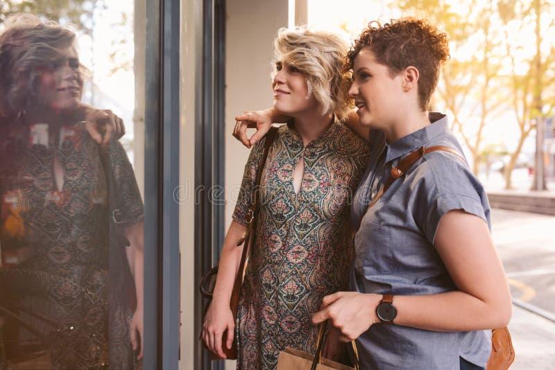 Усмехаясь молодое лесбосское окно пар ходя по магазинам совместно в городе стоковые фотографии rf