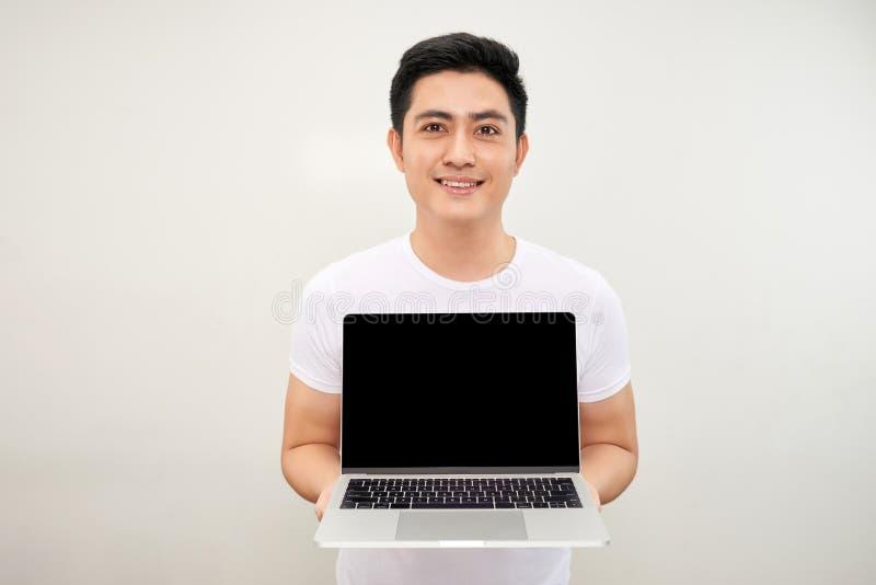 Усмехаясь молодой азиатский человек одетый в рубашке показывая ноутбук пустого экрана над белой предпосылкой стоковые изображения