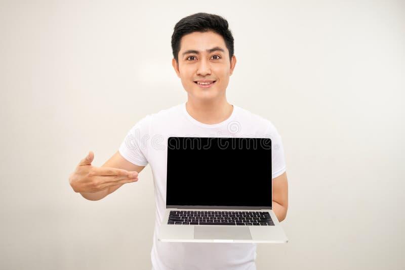 Усмехаясь молодой азиатский человек одетый в рубашке показывая ноутбук пустого экрана над белой предпосылкой стоковые фотографии rf