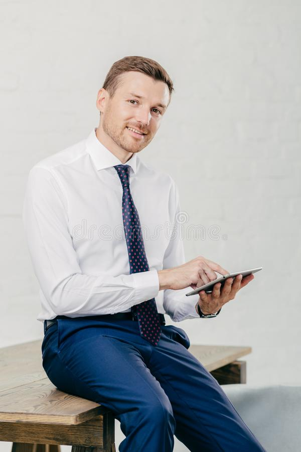 Усмехаясь молодой бизнесмен в элегантных одеждах счастливых для того чтобы получить сообщение дохода на современном планшете, сид стоковые изображения