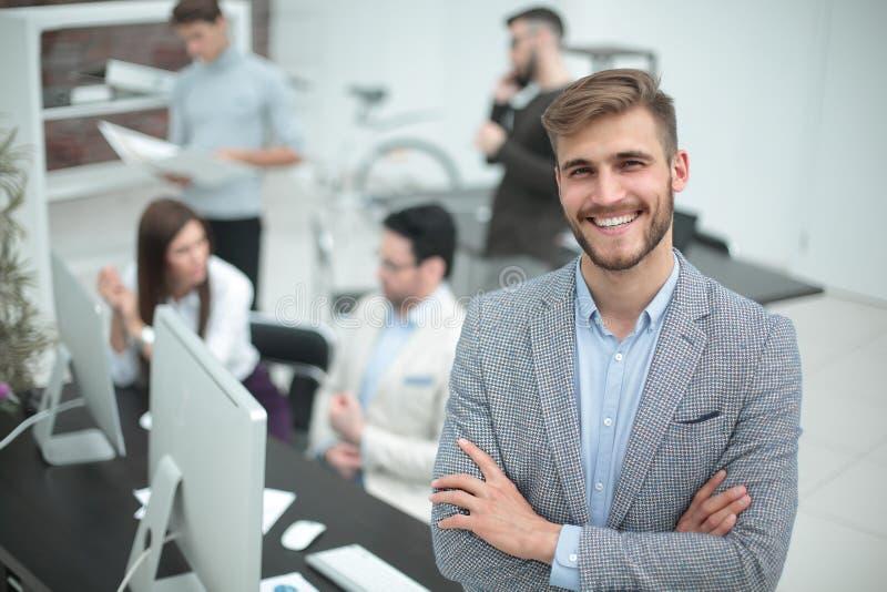 Усмехаясь молодой бизнесмен на заднем плане офиса стоковые фото