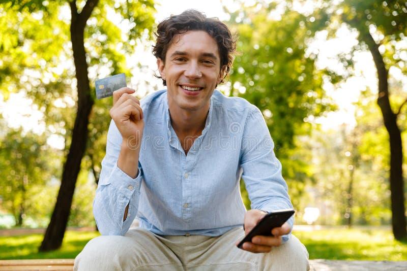 Усмехаясь молодой вскользь человек держа мобильный телефон стоковое фото