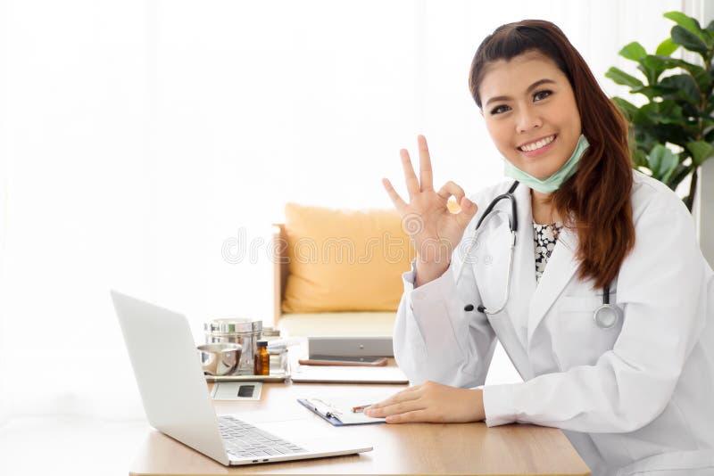 Усмехаясь молодой женский врач нести белое пальто с жестом ОК стоковая фотография rf