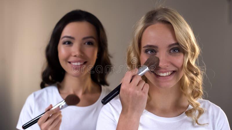 2 усмехаясь молодой женщины кладя вечер составляют и подготавливая для партии, красоты стоковая фотография rf