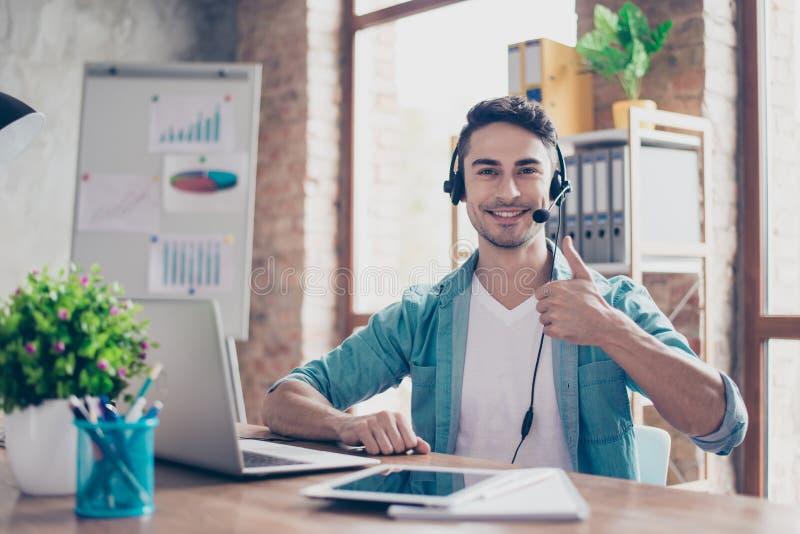 Усмехаясь молодой оператор центра телефонного обслуживания сидя на таблице и s стоковая фотография rf