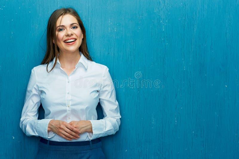 Усмехаясь молодой портрет бизнес-леди на голубой предпосылке стены стоковое изображение