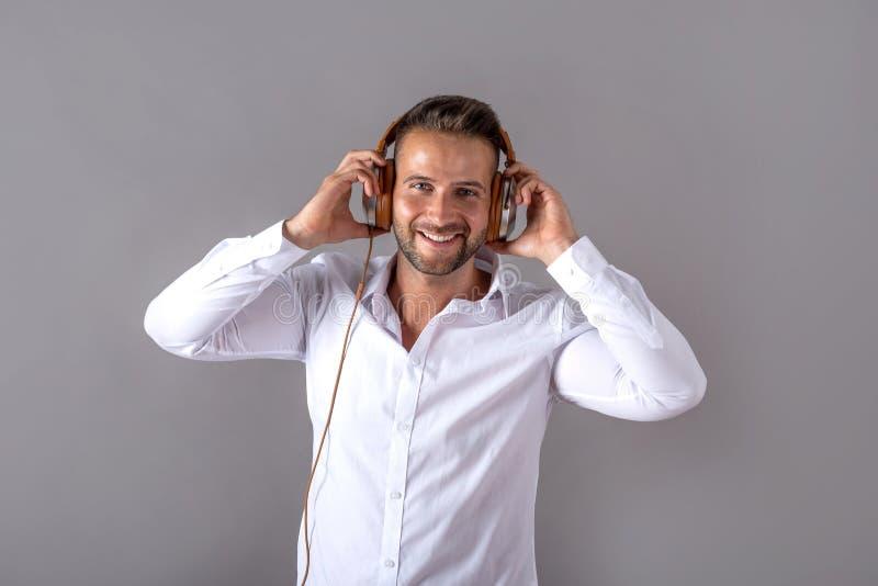 Усмехаясь молодой человек в белой рубашке слушая музыку стоковая фотография rf