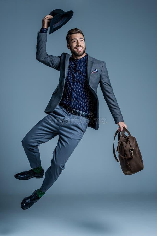 Усмехаясь молодой человек в костюме скача вверх и поднимать стоковые фотографии rf