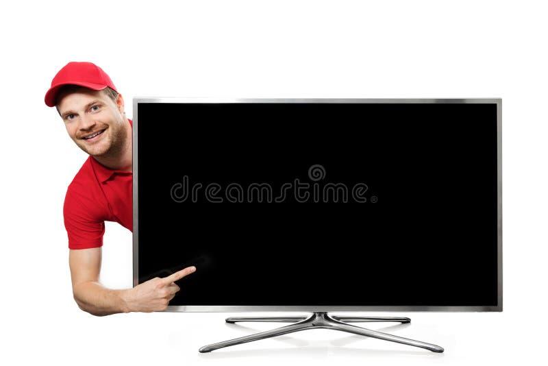 Усмехаясь молодой человек в красной форме указывая на пустой экран ТВ стоковая фотография