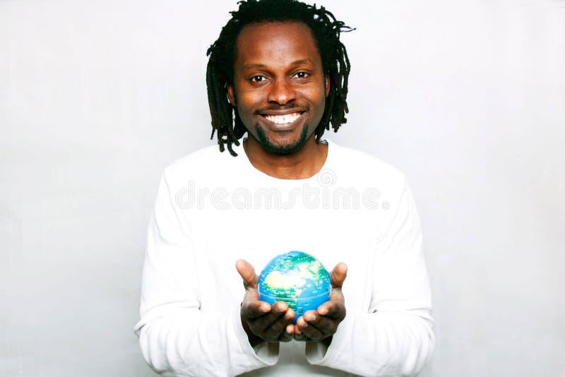 Усмехаясь молодой человек держит глобус мира в его руках стоковое фото