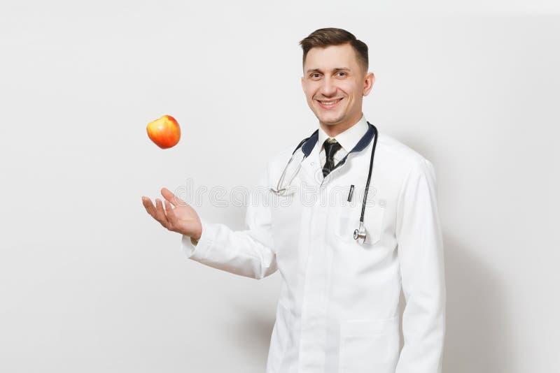 Усмехаясь молодой человек доктора изолированный на белой предпосылке Мужской доктор в медицинской форме, стетоскопе бросая вверх  стоковые фотографии rf