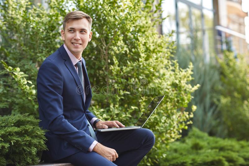 Усмехаясь молодой человек работая на компьтер-книжке пока сидящ outdoors владение домашнего ключа принципиальной схемы дела золот стоковое фото