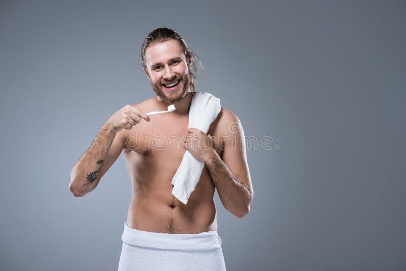 Усмехаясь молодой человек с полотенцем ванны на плече держа зубную щетку с зубной пастой в руке, стоковые изображения