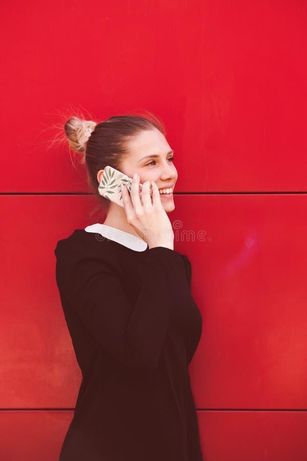 Усмехаясь молодой элегантный портрет бизнес-леди используя умный телефон стоковые изображения rf