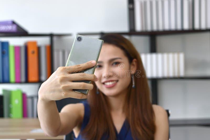 Усмехаясь молодые азиатские бизнес-леди принимая изображение или selfie в офисе стоковые изображения rf