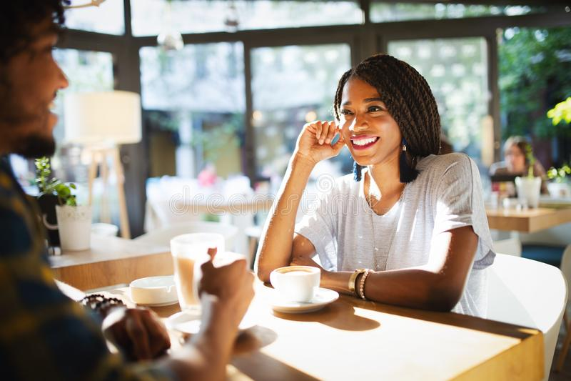 Усмехаясь молодые африканские пары сидя на таблице на кофе кафа выпивая и говоря совместно стоковое фото rf
