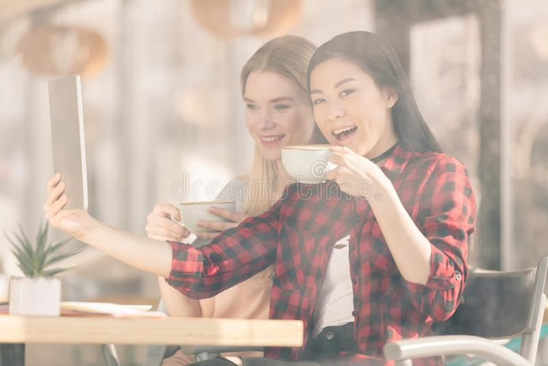 Усмехаясь молодые женщины выпивая кофе и использовать цифровой кофе планшета совместно стоковые изображения rf