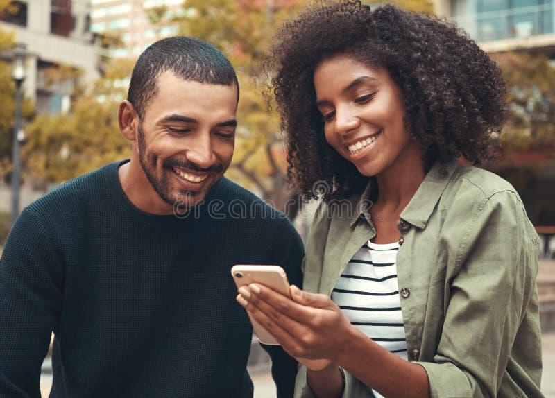 Усмехаясь молодые пары смотря смартфон стоковые изображения rf
