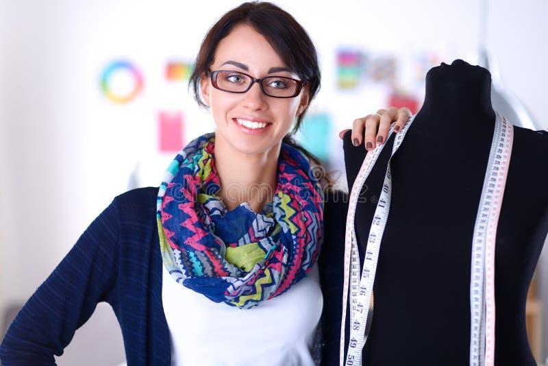 Усмехаясь модельер стоя близко манекен в офисе стоковые изображения