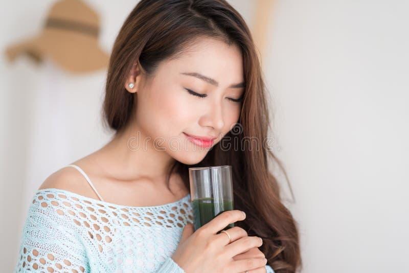 Усмехаясь молодая азиатская женщина выпивая зеленый свежий vegetable сок o стоковые фото