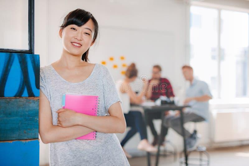 Усмехаясь молодая азиатская женщина стоя в офисе стоковая фотография rf